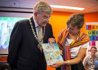Burgemeester Jan van Zanen van Utrecht, reikt het eerste exemplaar van het prentenboek van de Kinderboekenweek uit aan Marit Tornqvist, bij de opening van het boekenseizoen. © ANP.